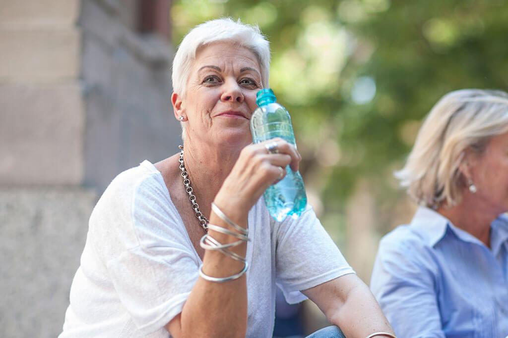 Eine Frau trinkt aus einer blauen Flasche.