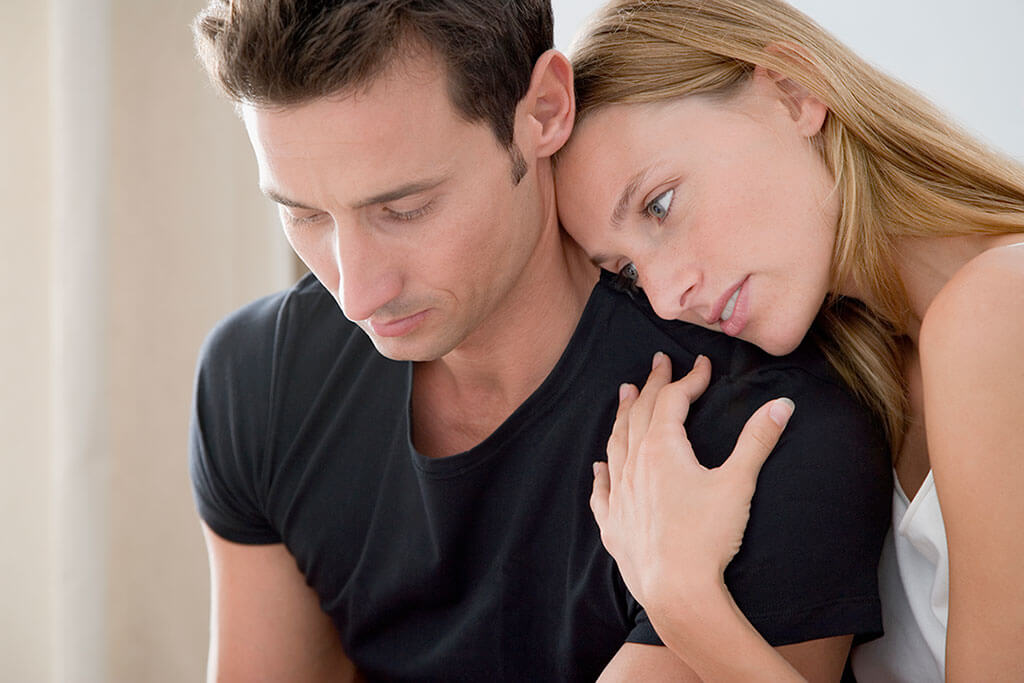 Eine Frau lehnt sich an die Schulter eines jungen Mannes.