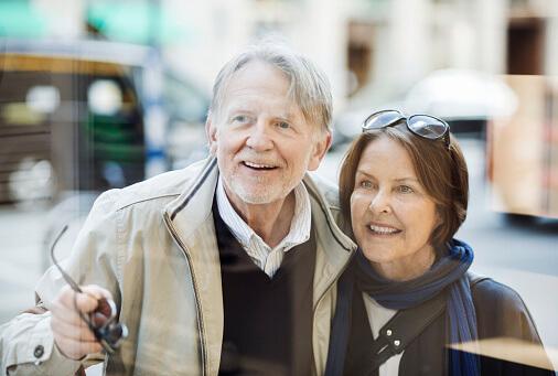 Ein älteres Paar schaut sich fröhlich ein Schaufenster an.