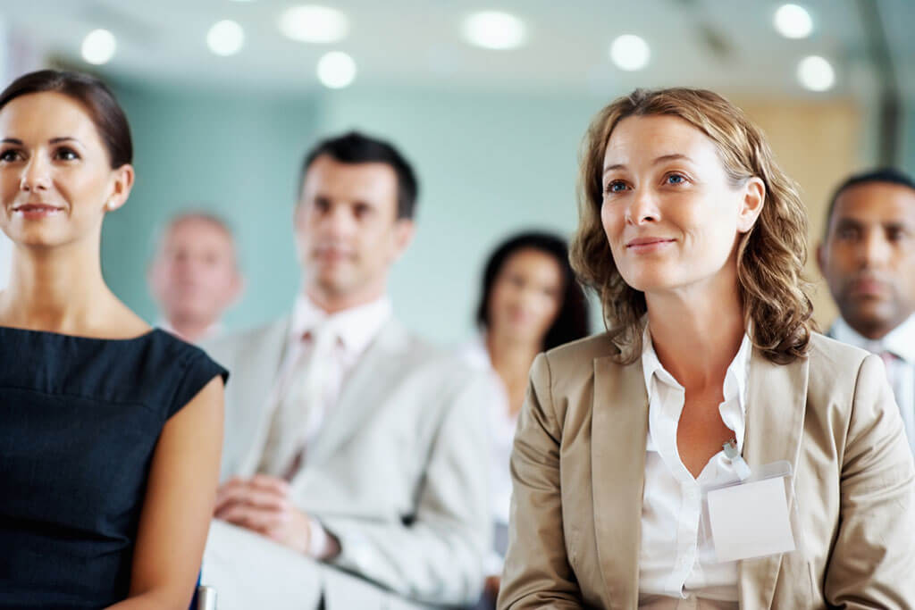 Frau sitzt interessiert mit anderen Personen in einem Saal.