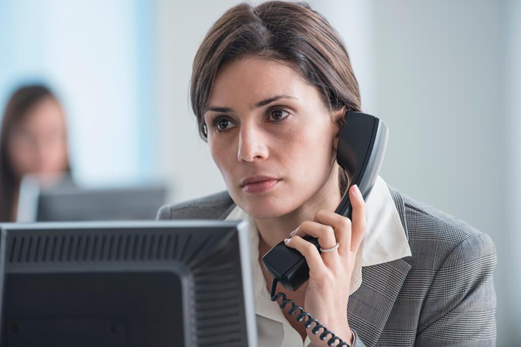 Frau sitzt im Büro und telefoniert.