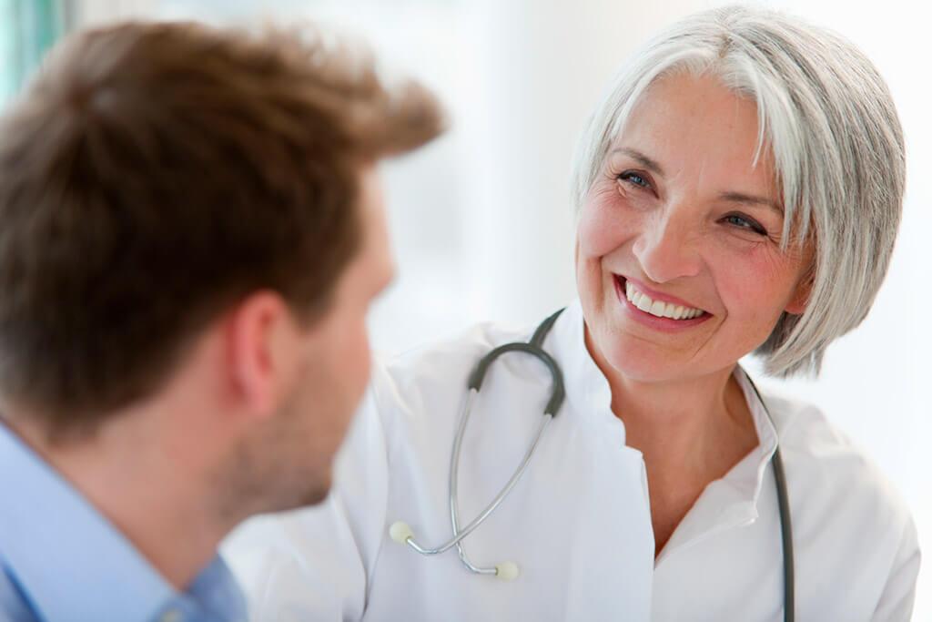 Ätere Ärztin lächelt einen Patienten an