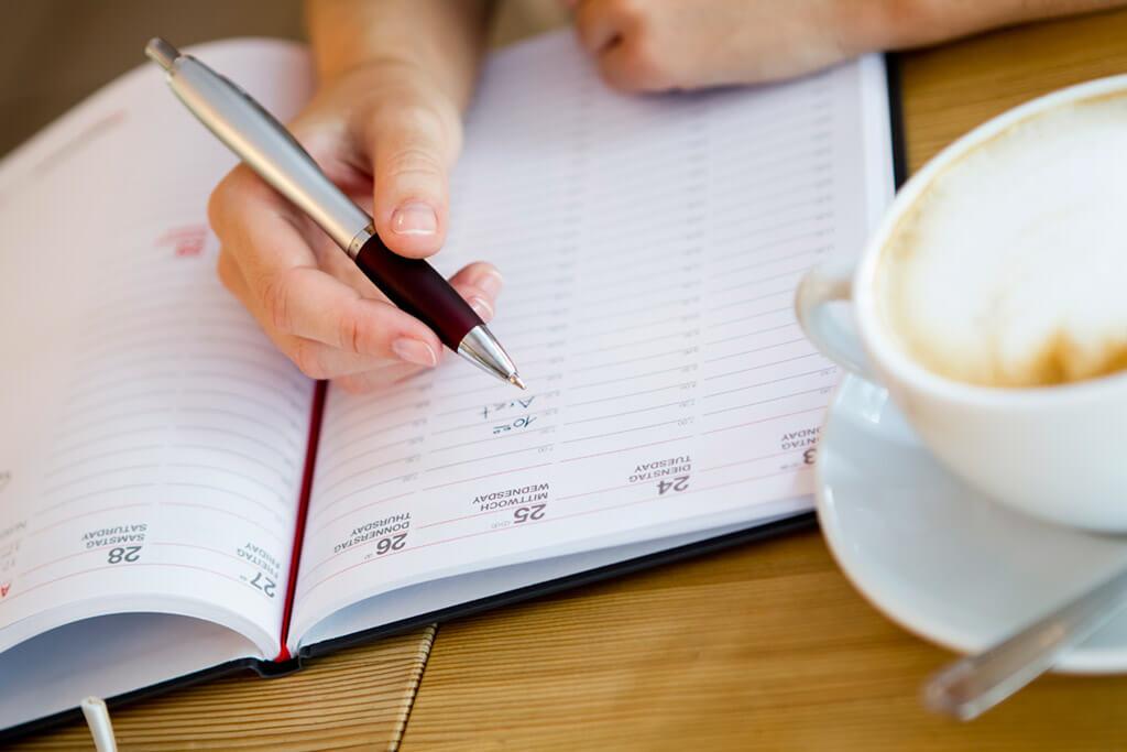 Eine Person hält einen Stift und schreibt etwas in einen Buchkalender