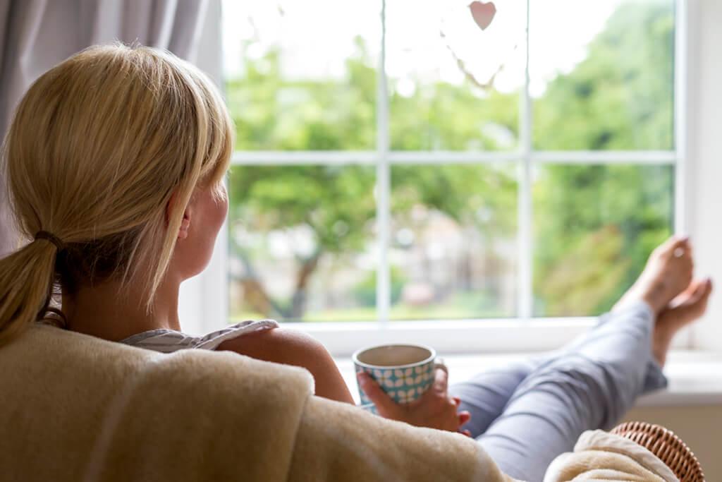 Frau mit Tasse in der Hand schaut aus dem Fenster