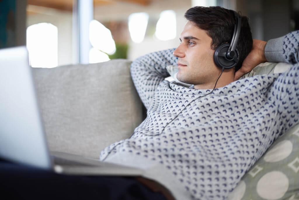 Junger Mann liegt auf dem Sofa und hört Musik.