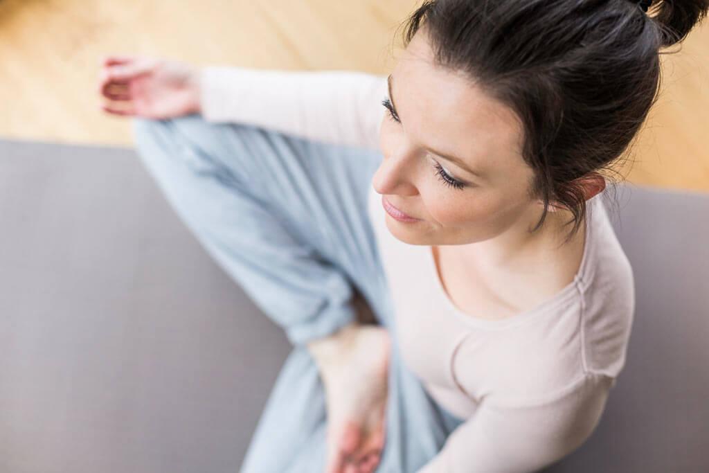 Junge Frau macht Yoga auf einer Matte.