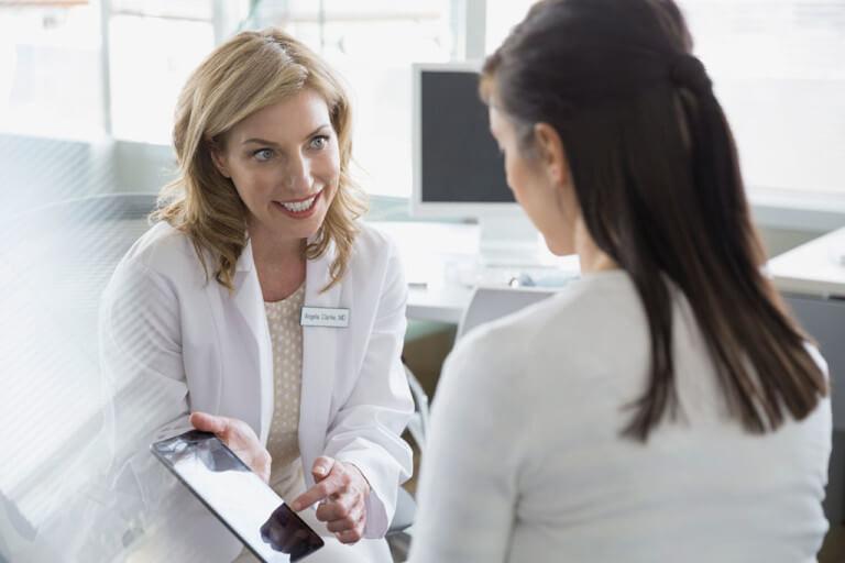 Mädchen bekommt etwas von einer Ärztin auf einem Tablet gezeigt.