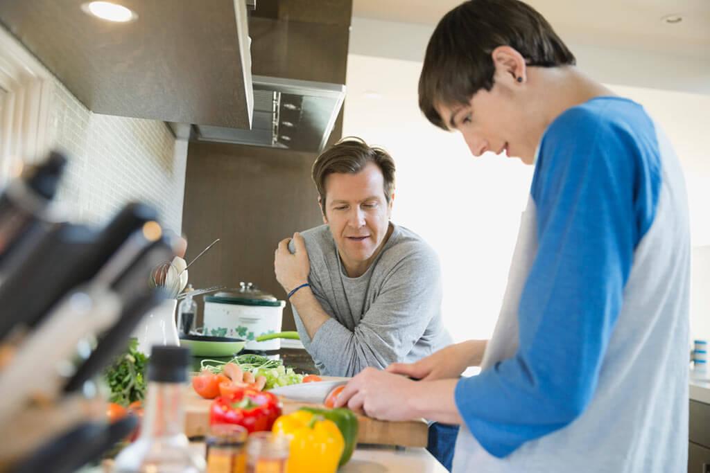 Junger Mann schneidet Gemüse in der Küche mit Vater.