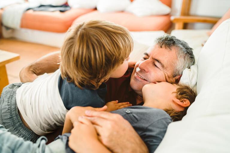 Vater kuschelt mit seinen zwei Söhnen auf dem Sofa.