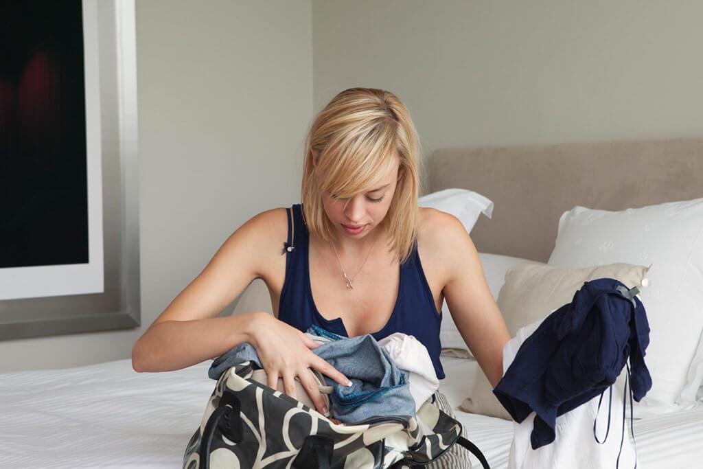 Junge Frau packt Ihre Reisetasche