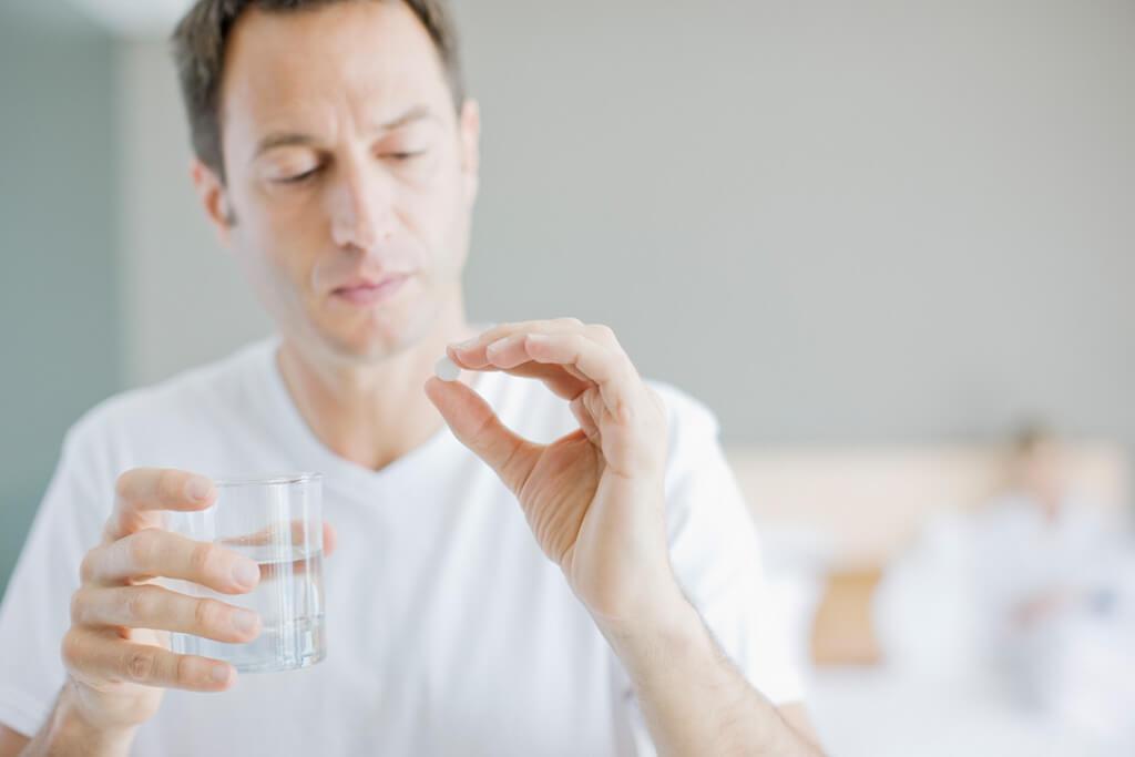 Mann hält ein Glas und eine Tablette in der Hand