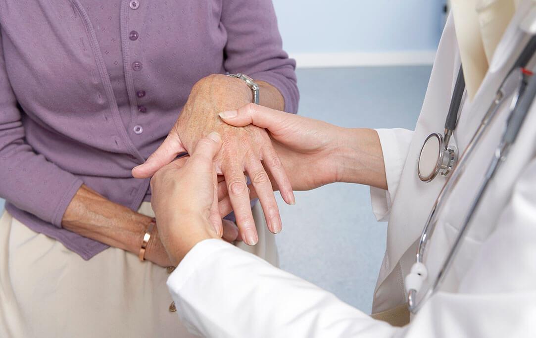 Eine Ärztin hält die Hand ihrer Patientin und untersucht diese.