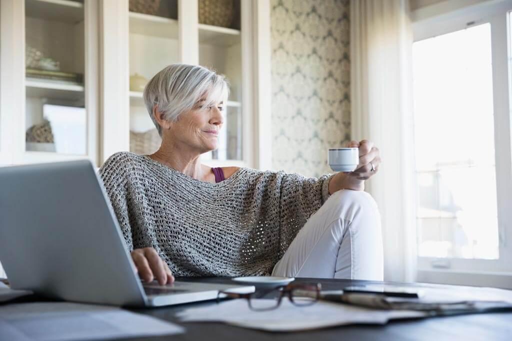 Frau mit Tasse schaut aus Fenster