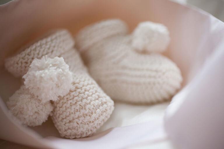 Weiße gestrickte Babyschuhe.