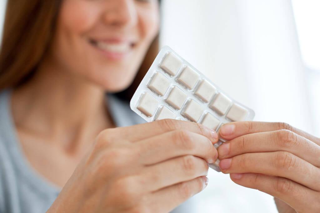 Eine Frau drückt Nikotinkaugummis aus einer Verpackung.