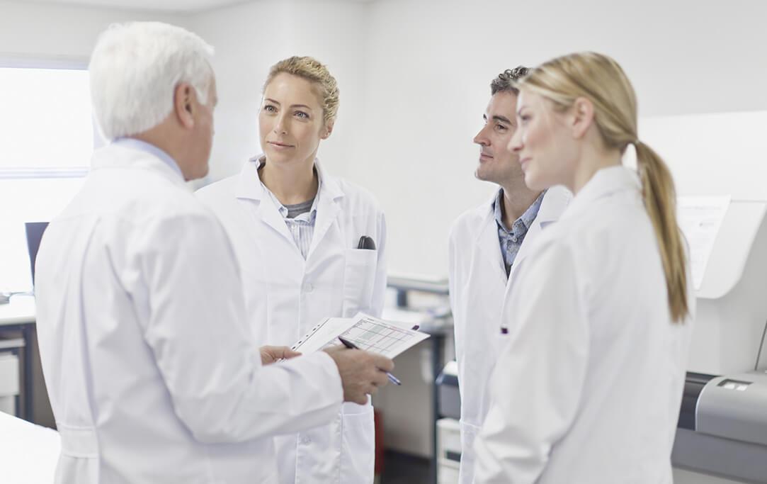 Vier Ärzte besprechen etwas zusammen.