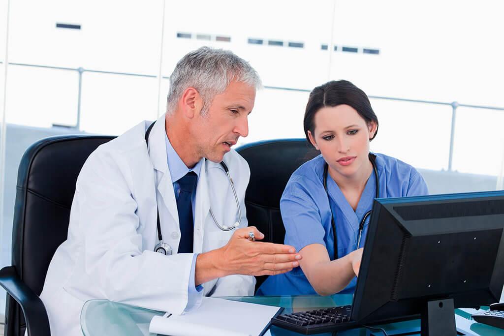Ein Arzt ist mit einer jungen Ärztin im Gespräch und zeigt dabei auf den Bildschirm eines Computers