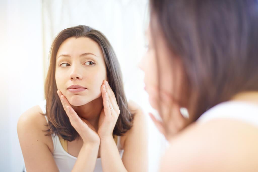 Frau prüft im Spiegel ihre Haut im Gesicht.