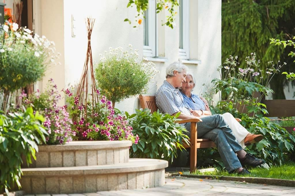Altes Ehepaar sitzt auf einer Bank im Garten