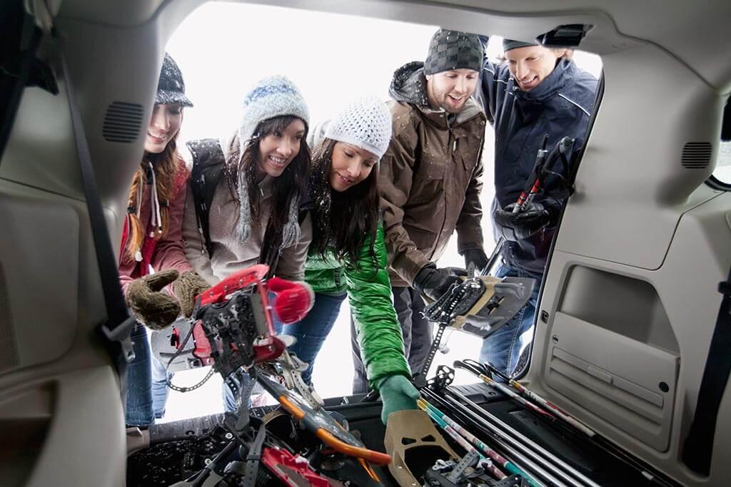Eine Gruppe von jungen Menschen räumen ihre Skisachen in das Auto hinein.