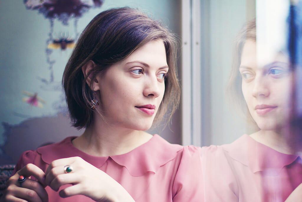 Frau schaut nachdenklich aus einem Fenster.