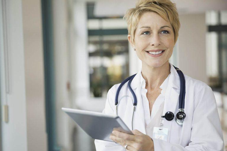 Eine fröhliche Ärztin mit einem Tablet in der Hand.
