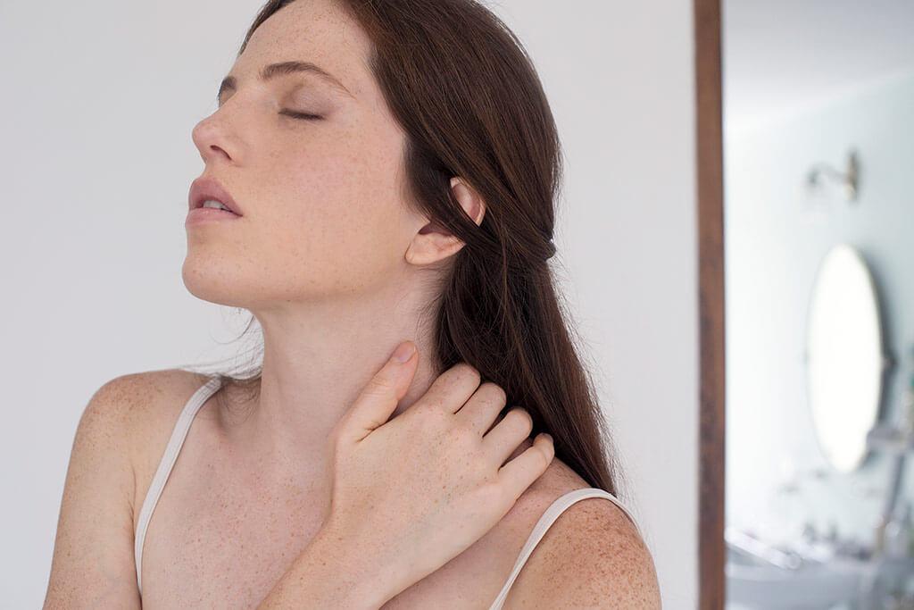 Frau hebt sich schmerzhaft am Nacken.