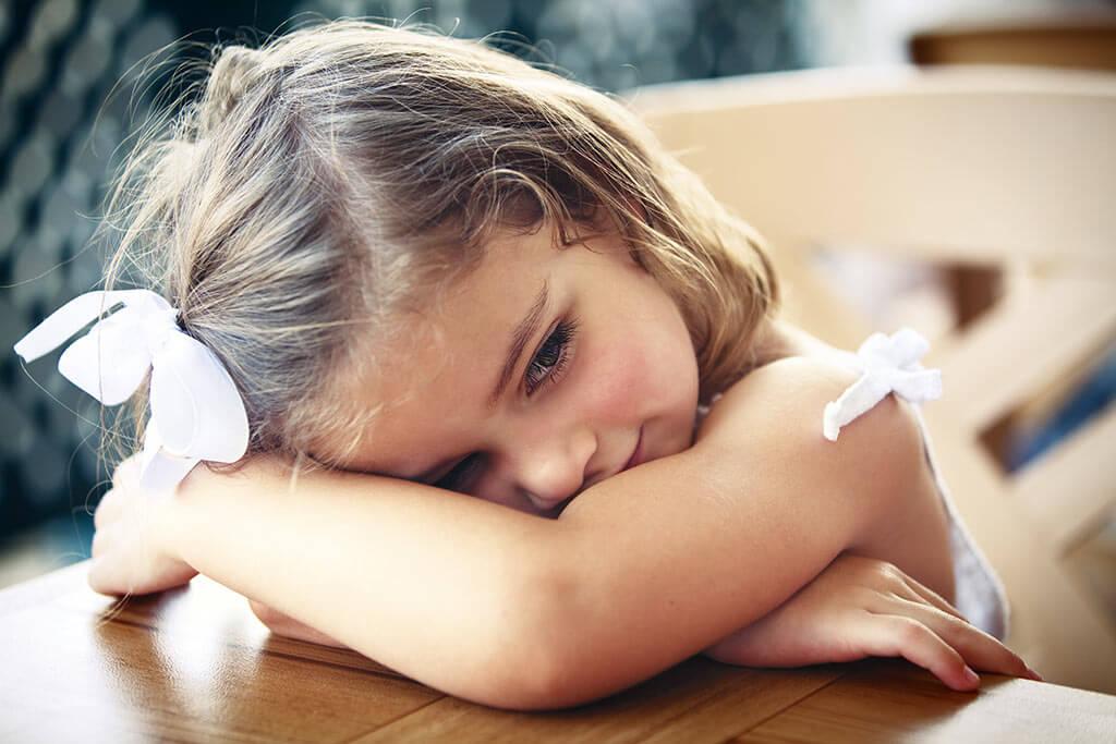 Mädchen liegt mit dem Kopf auf einem Tisch und lächelt.
