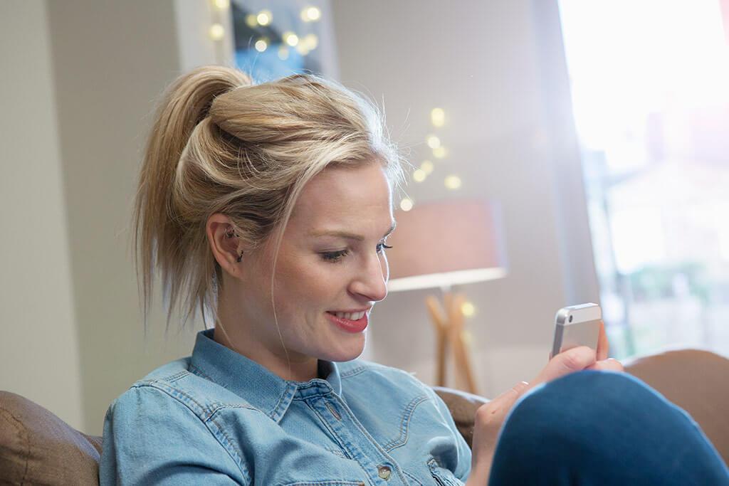 Junge Frau lächelt ihr Handy an.