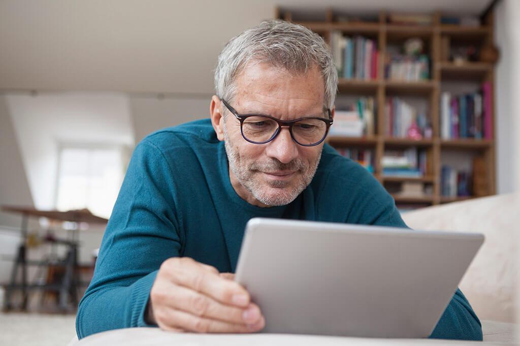 Älterer Mann schaut auf sein Tablet.
