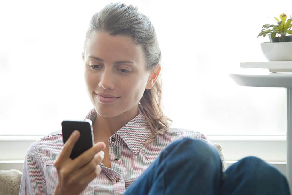 Eine Frau schaut auf ihr Handy.