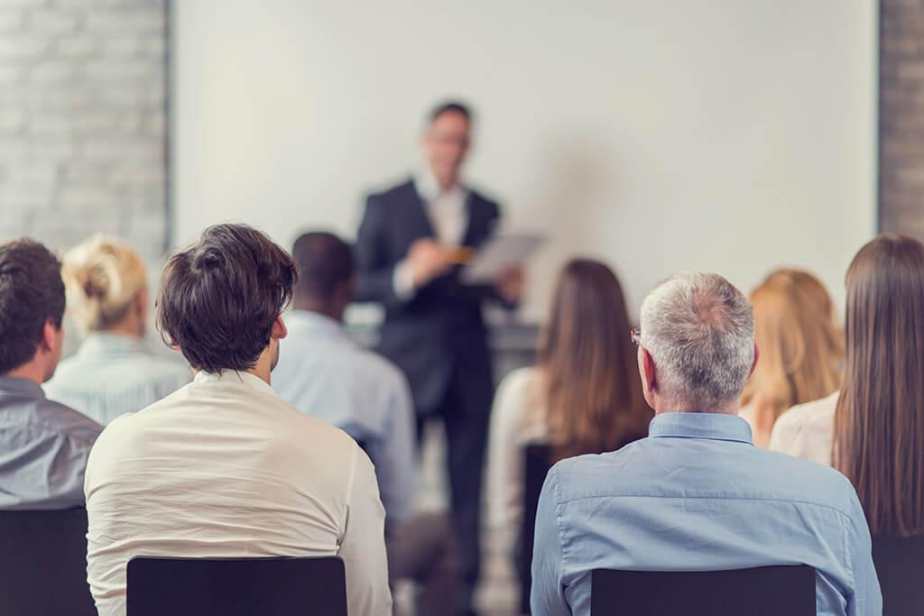 Mehrere Personen verfolgen einen Vortrag.