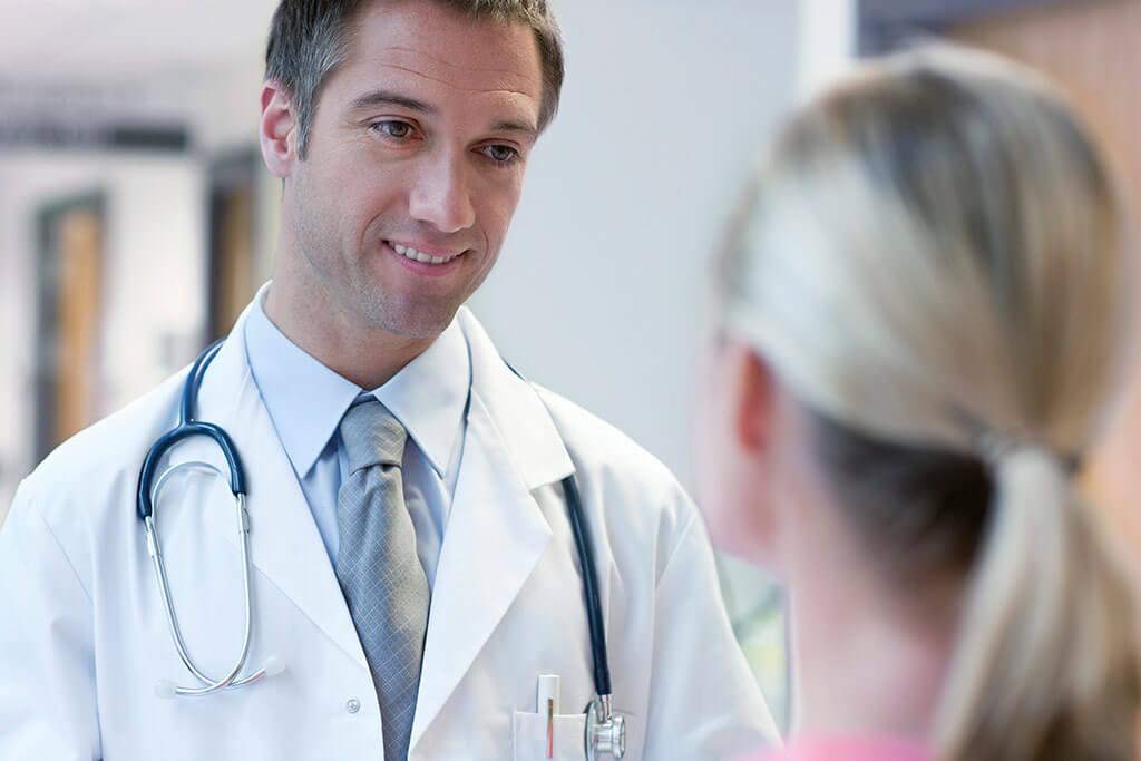 Junger Arzt lächelt seine Patientin an.