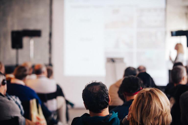 Mehrere Personen hören einem Vortrag zu.