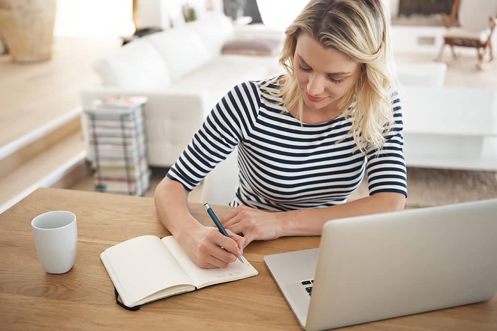 Junge Frau sitzt am Tisch mit ihrem Laptop und notiert sich etwas in ein Notizbuch.