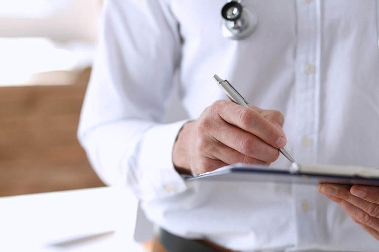 Ein Arzt notiert sich etwas auf seinem Klemmbrett.