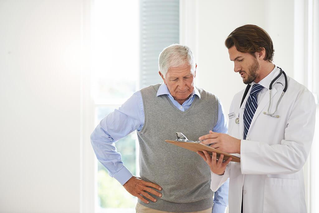 Ein Arzt zeigt einem älteren Mann etwas auf einem Klemmbrett.
