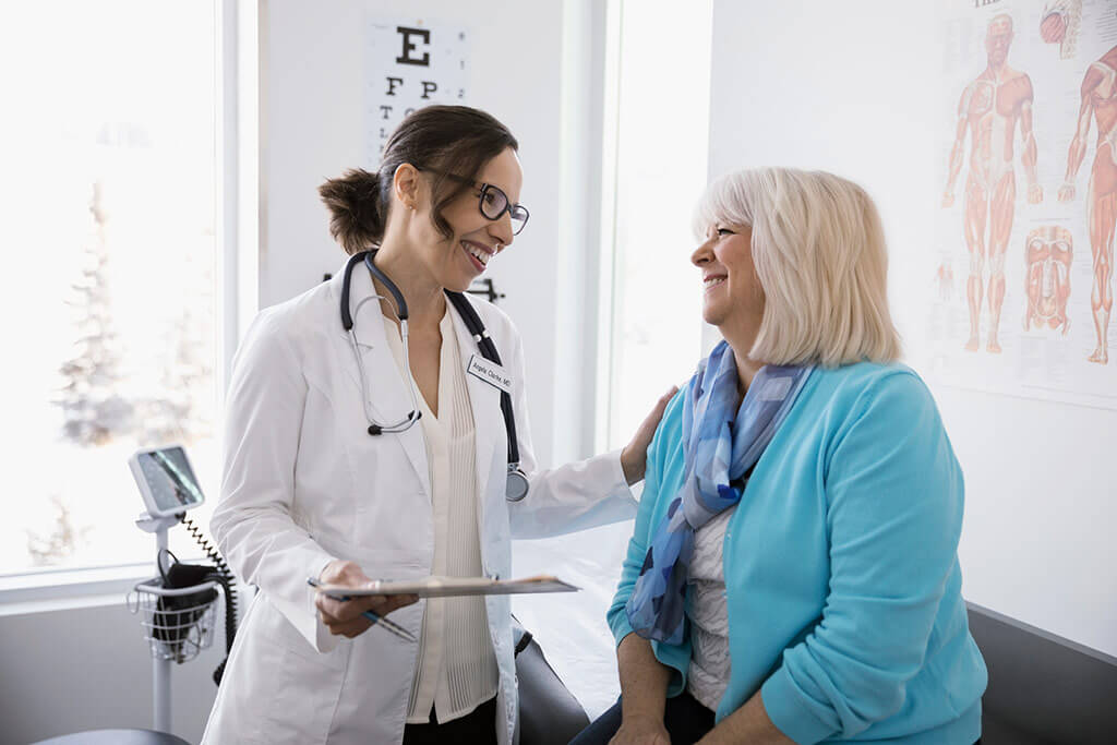 Ärztin legt lächelnd ihre Hand auf die Schulter einer älteren Patientin