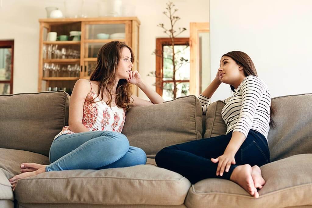 Zwei Mädchen sitzen zusammen auf einem Sofa und erzählen sich etwas.