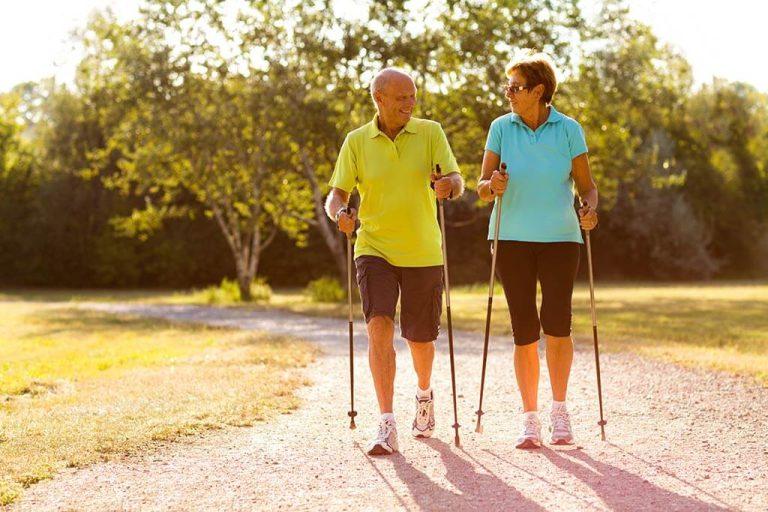 Ein älteres Paar macht zusammen Nordicwalking.