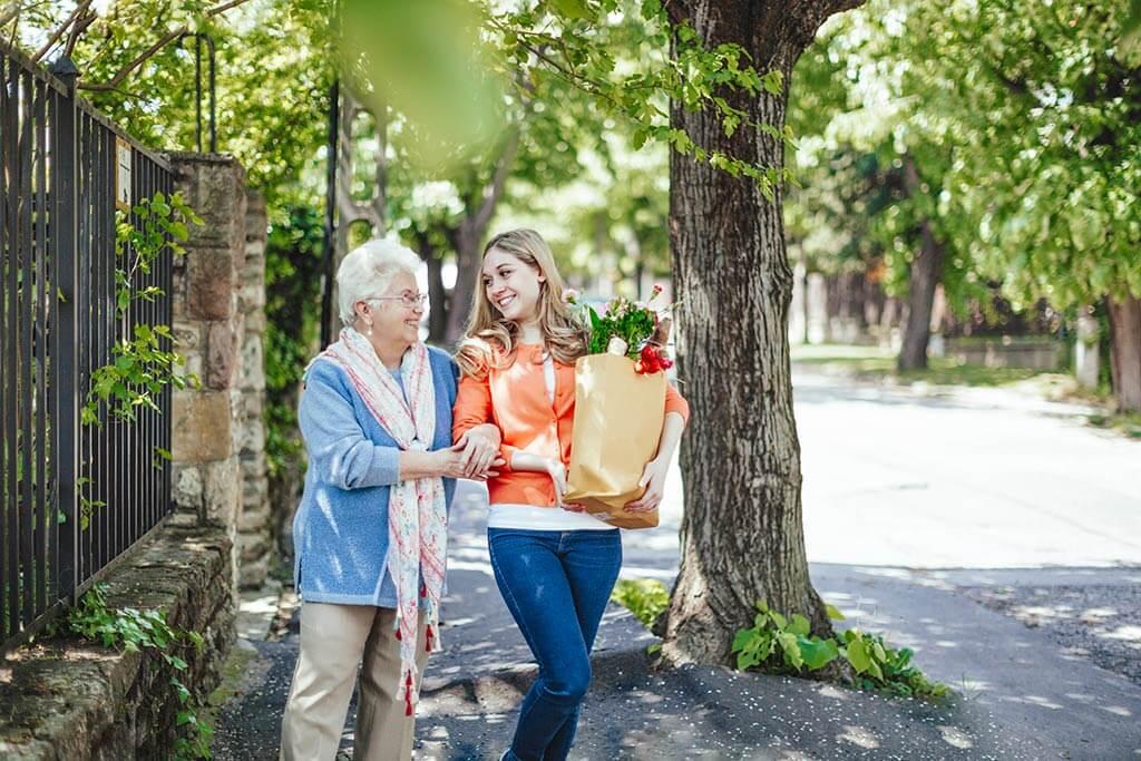 Ein junges Mädchen hilft einer älteren Frau beim Einkaufstaschen tragen.