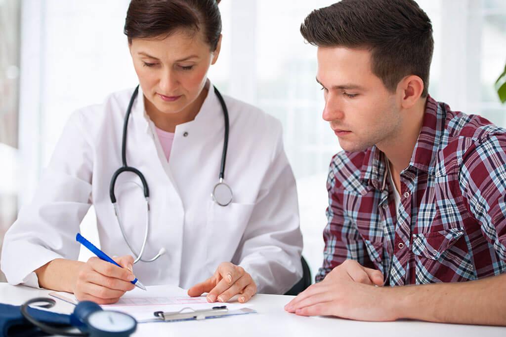 Eine Ärztin erklärt einem jungen Mann etwas.