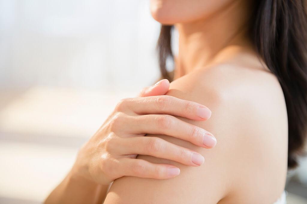Eine Frau legt sich Ihre Hand auf die Schulter.