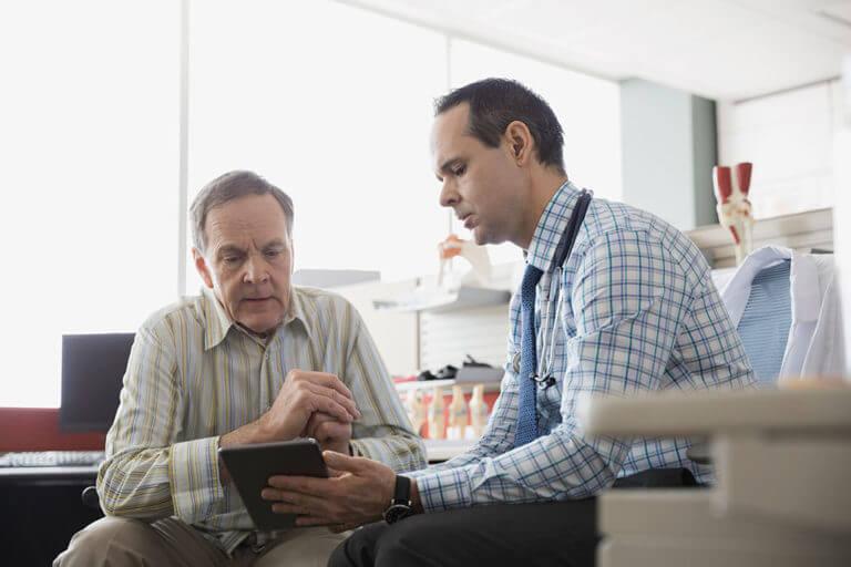 Ein Arzt zeigt einem älteren Mann etwas auf einem Tablet.