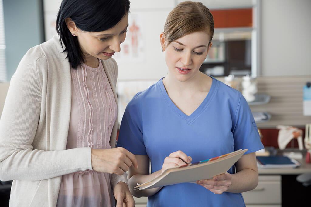 Eine Frau bespricht etwas mit einer Krankenschwester.