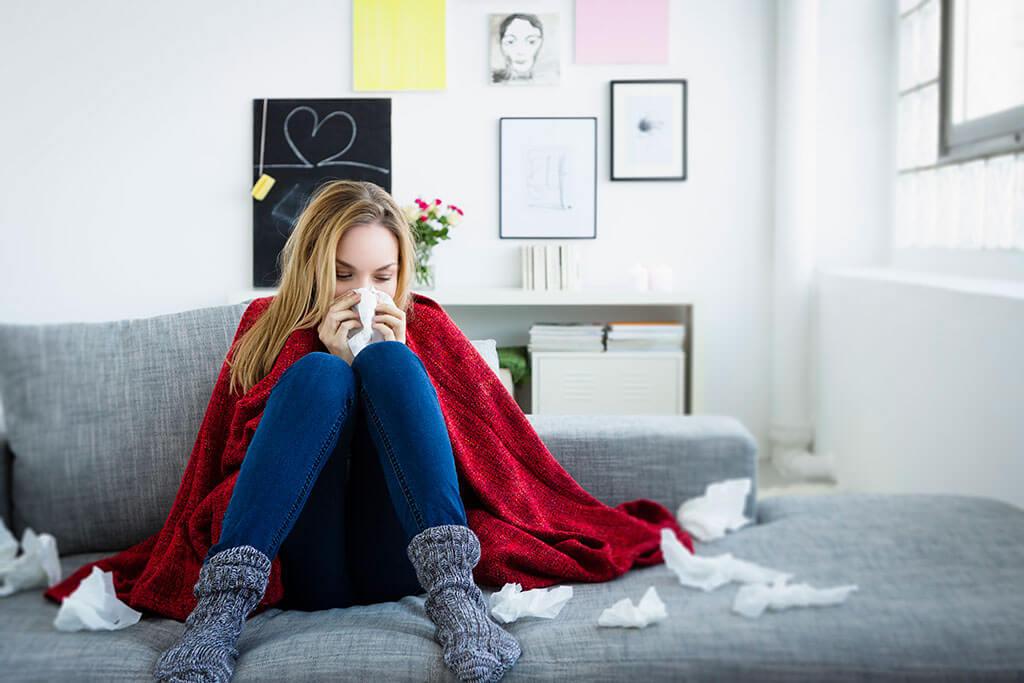 Junge Frau sitzt verschnupft mit vielen Taschentüchern auf einem Sofa.