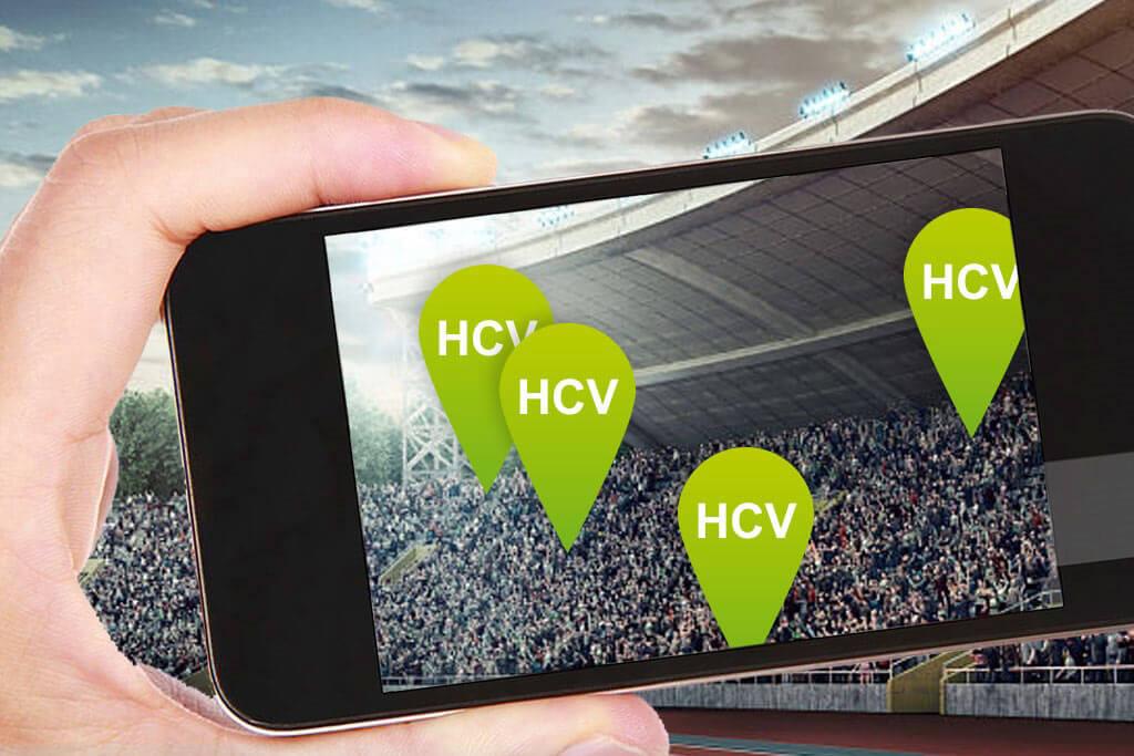 Eine Hand mit einem Smartphone fotografiert die Menschenmenge in einem Stadion.