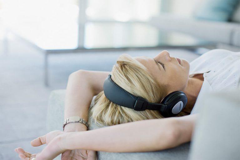 Frau liegt mit Kopfhörern auf einem Sofa.