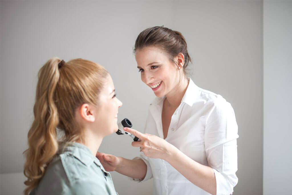 Hautärztin untersucht die Haut eines jungen Mädchens.