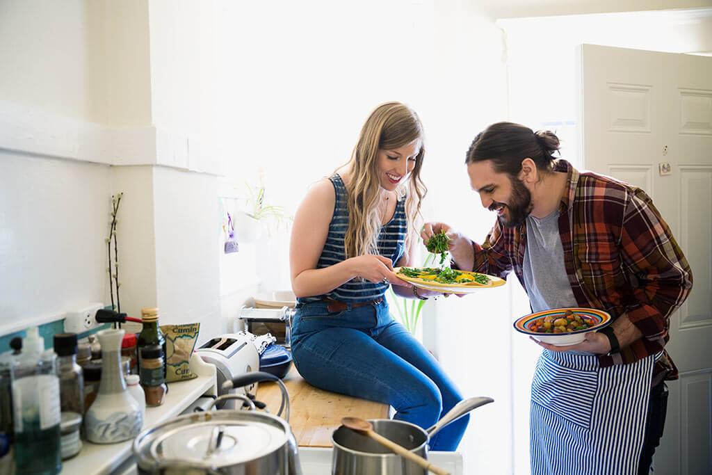 Ein junges Paar kocht zusammen in einer Küche.